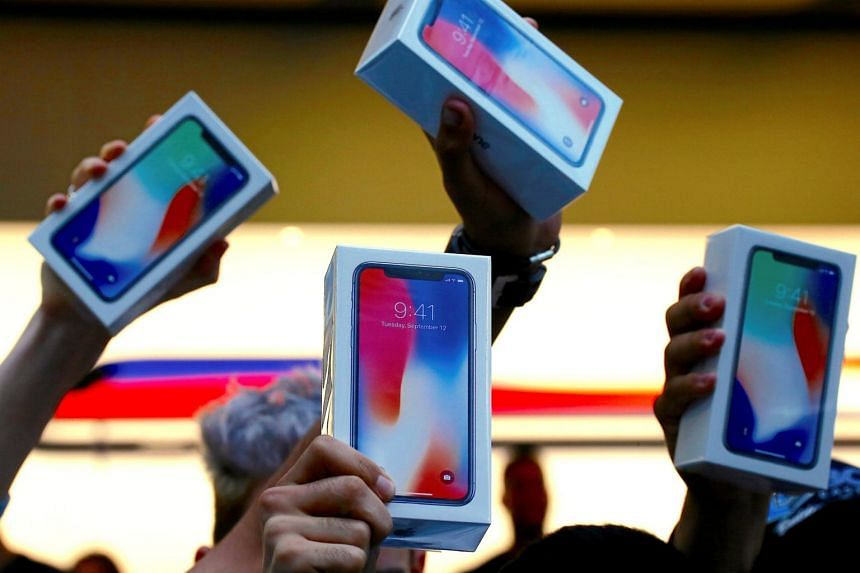 The first customers to buy the iPhone X hold it aloft during the global launch of the new Apple product in central Sydney.