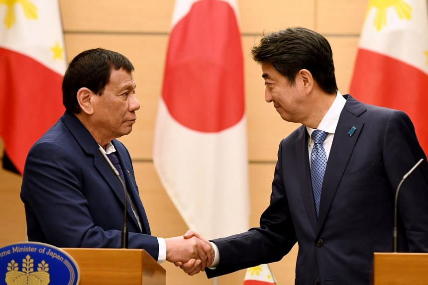 Philippines President Rodrigo Duterte shakes hands with Japanese Prime Minister Shinzo Abe at the end of their signing ceremony and joint remarks announcement at Abe's official residence in Tokyo.