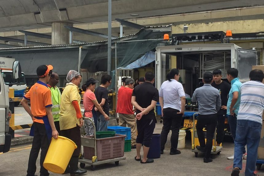 Store keepers queueing for water. ST understands that water supply to Tampines bus interchange and the food court at Eastlink Mall is affected.