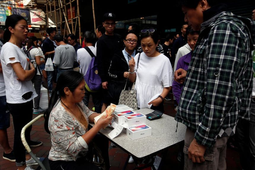 A woman buys new iPhone Xs that people who just bought from Apple Stores are reselling, on a street in Hong Kong on Nov 3, 2017.