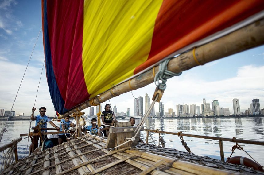 Deckhands aboard a replica of a traditional Philippine wooden boat, known as a balangay, sailing their craft in Manila Bay. The replica of the ancient boat, which dates back as far as AD320, is one of two that will make a six-day journey to southern