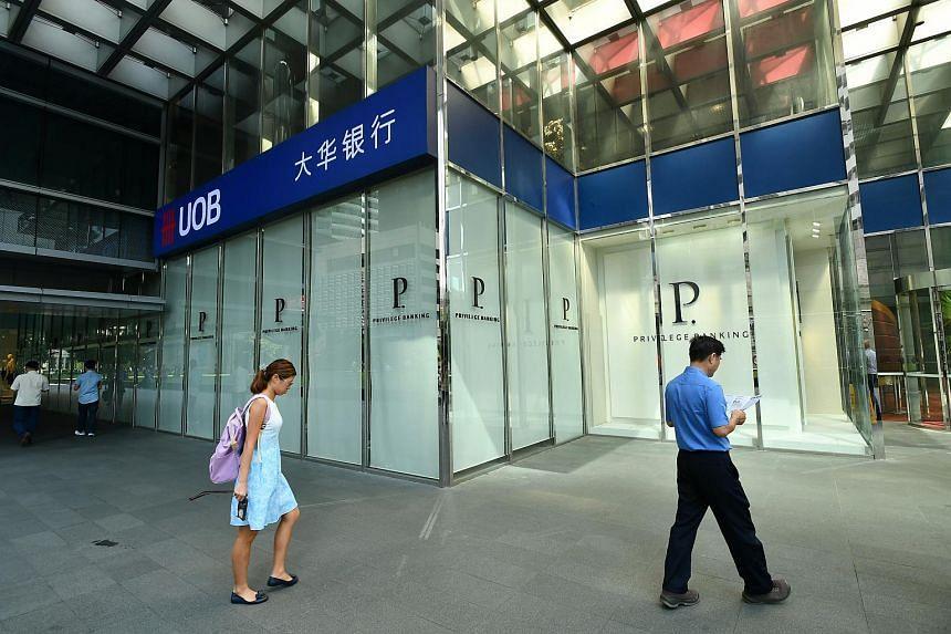 Pedestrians walk pass a UOB branch at Raffles Place.