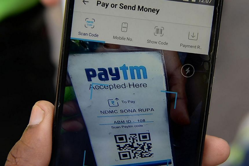 A customer scans a bar code sign of cellphone-based payment system Paytm at a parking area in New Delhi.