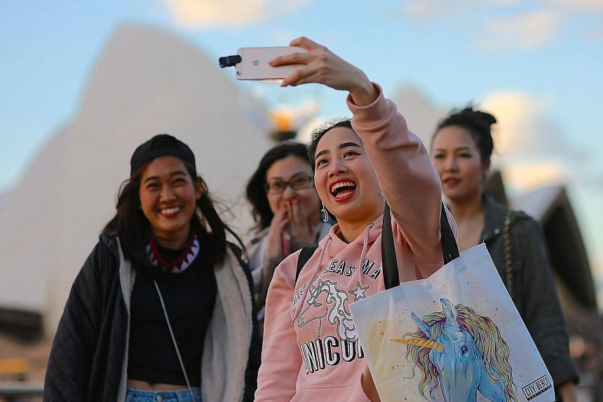 Tourists taking a wefie in front of the Sydney Opera House.