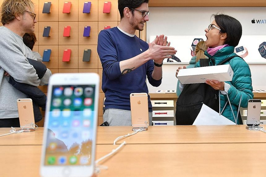 A customer shopping at an Apple store in San Francisco. Apple said it sold 46.7 million iPhones in the fourth quarter ended Sept 30, above analysts' estimates of 46.4 million. Analysts have been eager to see whether Apple can meet demand for the iPho