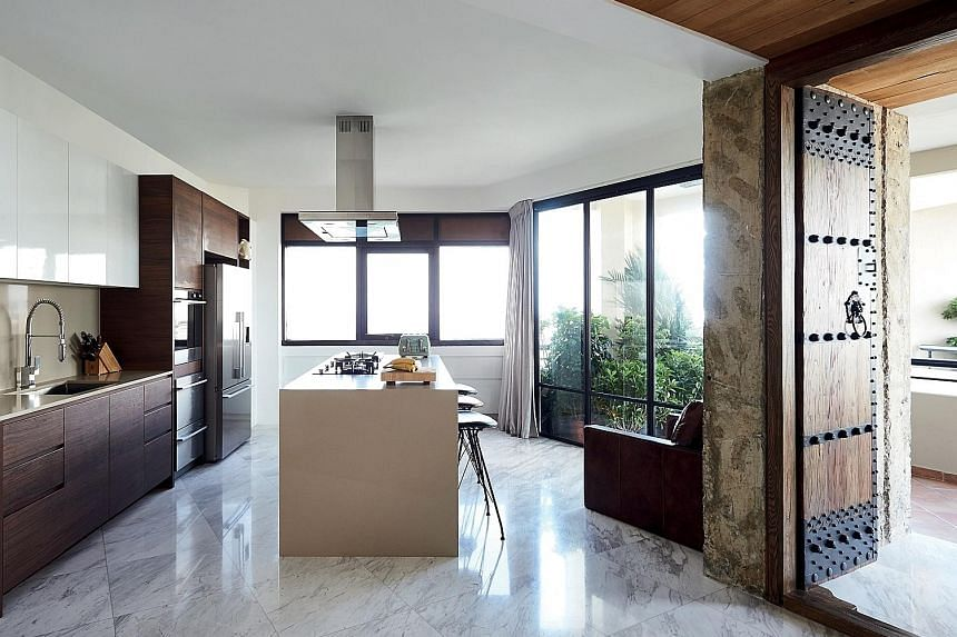 The kitchen island (above) is where the friends of Mr Richard Lee (left) and his wife gather over drinks and to take in the panoramic views of the sea. With the new layout, the space now flows seamlessly to the living and dining areas (right).