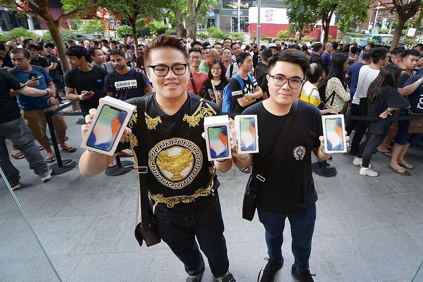 University students Supakorn Rieksiri (far left) and Kittiwat Wang flew in from Thailand to collect yesterday the two iPhones each that they pre-ordered on Oct 27.