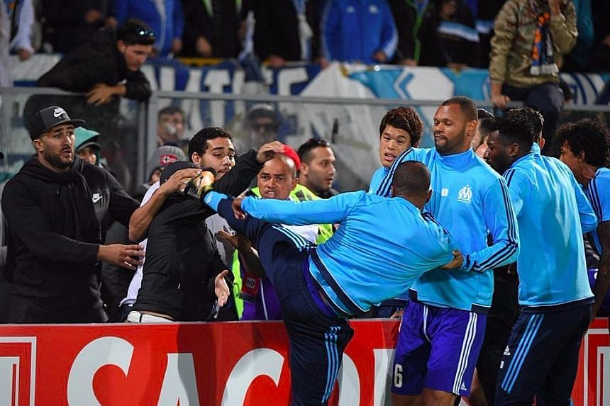 Marseille defender Patrice Evra aiming a kick at a fan before their Europa League tie at Vitoria Guimaraes. Uefa have levelled a violent conduct charge against him, which will be heard next Friday.