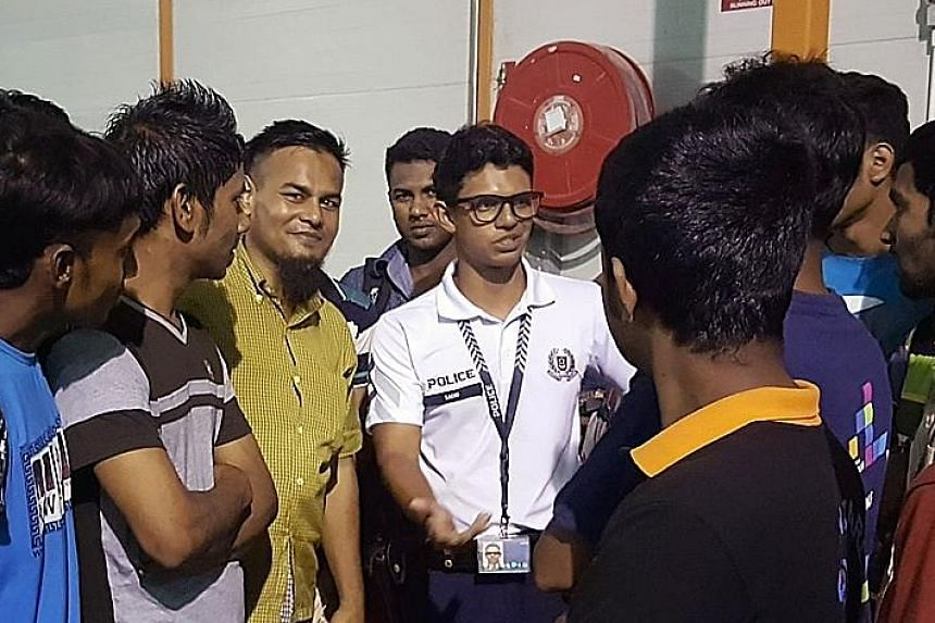 Special Constable Corporal Nabel Al Masri (centre) chatting with foreign workers. His fluent Bengali helps him connect with the workers, making it less intimidating for them to approach the police for help