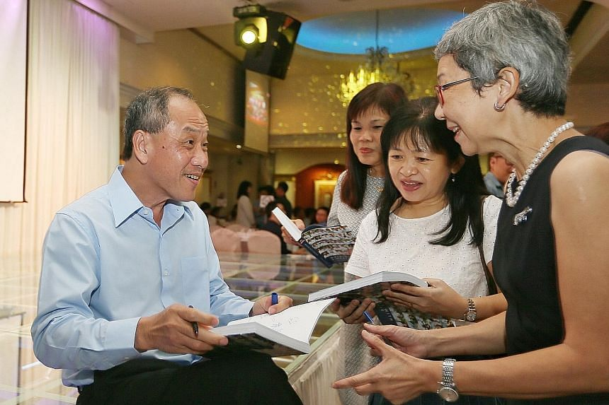 WP secretary-general Low Thia Khiang signing copies of the party's 60th anniversary commemorative book, Walking With Singapore, at the celebratory dinner last night. Mr Low, who entered politics in 1988, would have led the party for 17 years when he