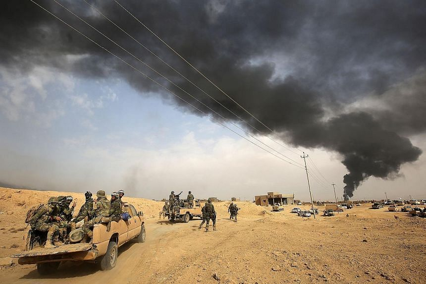 Iraqi forces and members of the Hashed al-Shaabi (Popular Mobilisation Units) advancing towards the city of Al-Qaim, in Iraq's western Anbar province near the Syrian border, as they fight against remnant pockets of Islamic State in Iraq and Syria mil