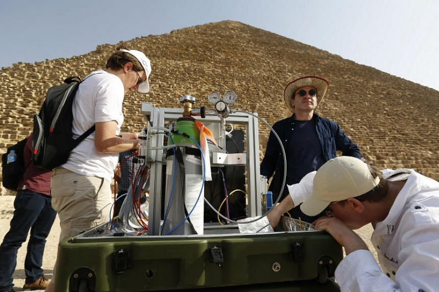 Researchers prepare a device during scanning using cosmic rays in front of the Khufu's Pyramid in Giza, Egypt on May 30, 2016