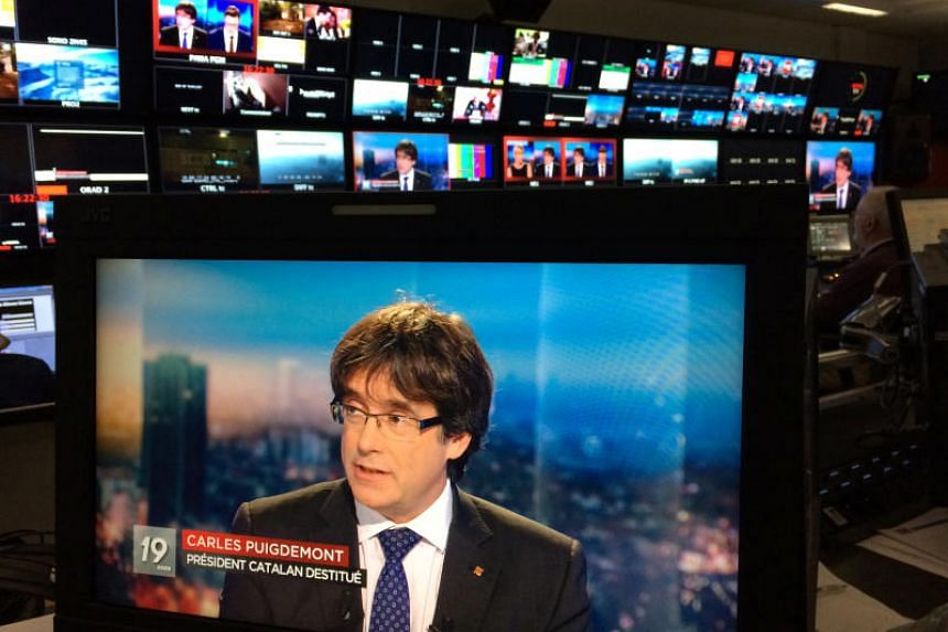 Ousted Catalan President Carles Puigdemont appears on a monitor during a live TV interview on a screen in a bar in Brussels, Belgium, on Nov 3, 2017.