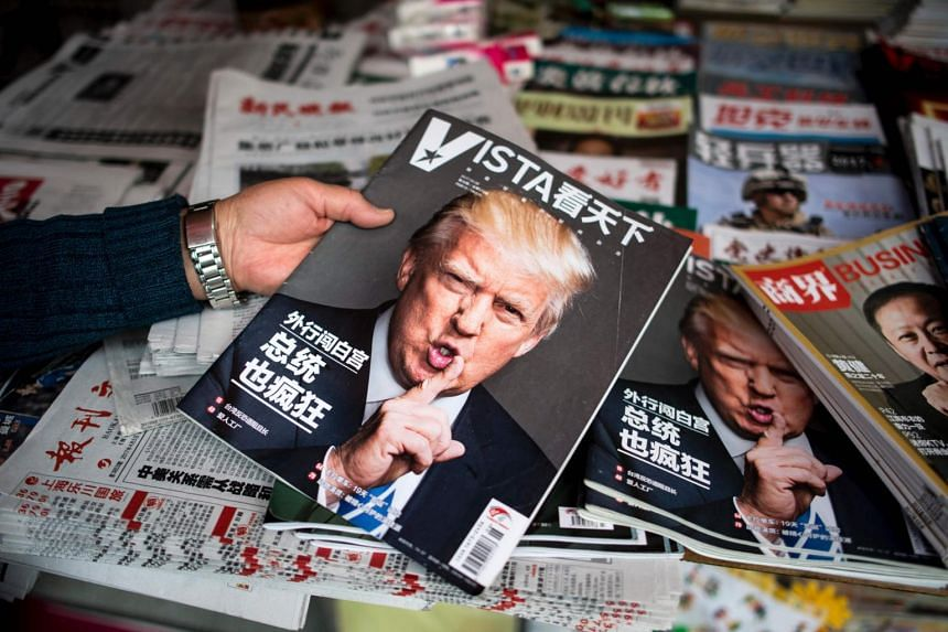 A woman holds a Chinese newspaper with a picture of US President Donald Trump at a news stand in Shanghai.