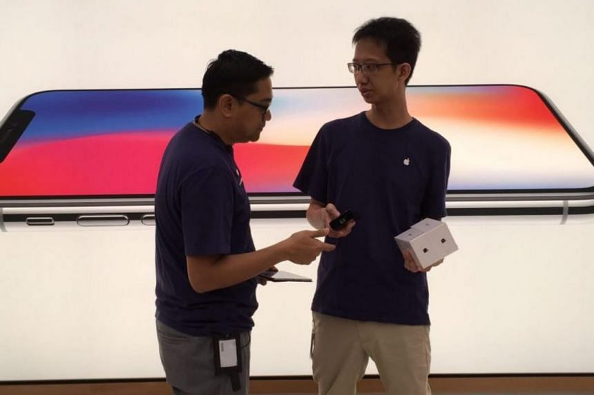 An Apple staff provides assistance to a customer at the Apple store in Orchard Road.