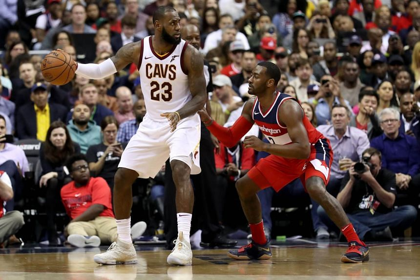 LeBron James #23 of the Cleveland Cavaliers dribbles the ball against John Wall #2 of the Washington Wizards.