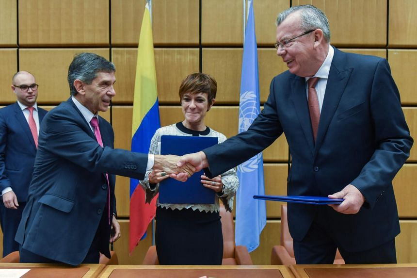 Colombia's special post-conflict envoy and Labour Minister Rafael Pardo Rueda (left) shakes hands with United Nations Office on Drugs and Crime (UNODC) Executive Director Yury Fedotov (right) as Colombia's director of Agency of Renovation of Territor
