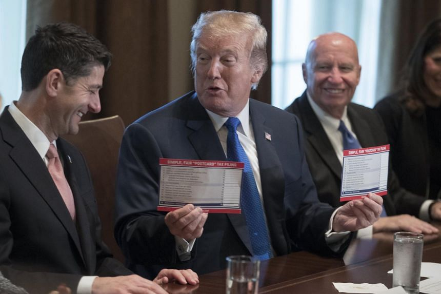 US President Donald Trump (centre) holds up samples of tax filing 'postcards' beside US Speaker of the House Paul Ryan (left) and Chairman of the House Ways and Means Committee Kevin Brady.