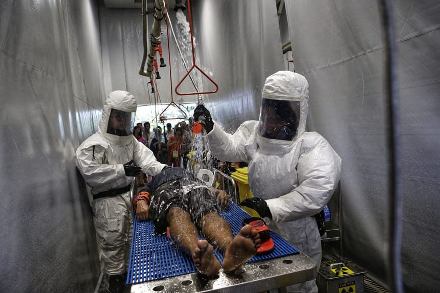"The decontamination team decontaminates the ""casualty"" during a full dress rehearsal at Ng Teng Fong General Hospital."