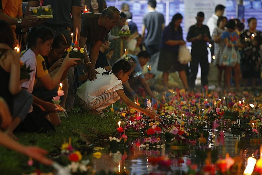 By the light of a full moon on Friday to celebrate Loy Krathong, Thais gathered with friends and family to release flower-shaped floats into canals, rivers and lakes, in a symbolic liberation from past negativity and transgressions.