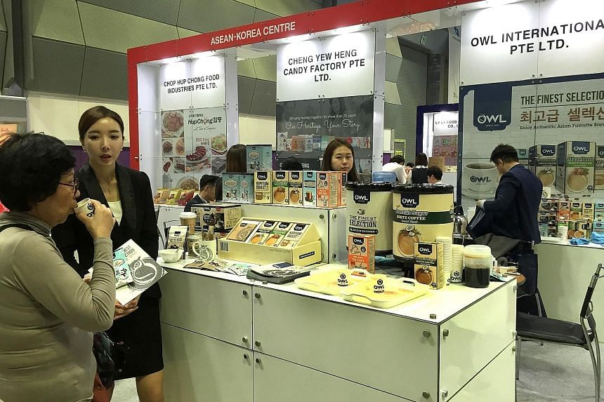A visitor tasting coconut coffee at Owl's booth at the Asean Trade Fair held in Seoul, South Korea, last week.