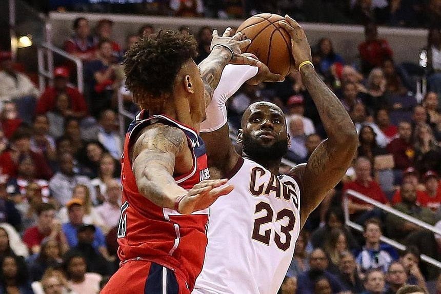 Cleveland Cavaliers forward LeBron James going for a shot despite the close attention of Washington Wizards forward Kelly Oubre Jr at Capital One Arena. The Cavaliers won 130-122, as James came just four points short of his career-best score.