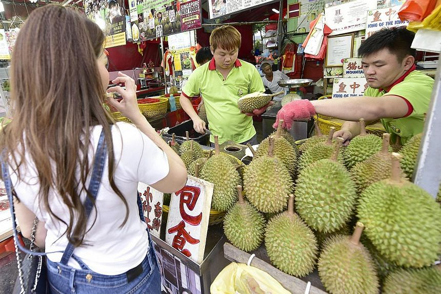 """Sellers doing business at Combat Durian in Balestier Road. The vendor saw sales drop by 20 to 30 per cent during the last season in June and July owing to the higher prices, but owner Linda Ang said: """"Hopefully, with more supply coming from Pahang an"""