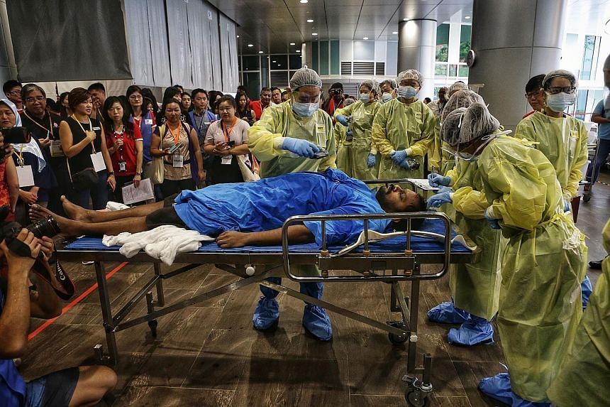 """The radiation response team scanning a """"casualty"""" for radioactive or contaminated substances in the lobby of Ng Teng Fong General Hospital during yesterday's event."""