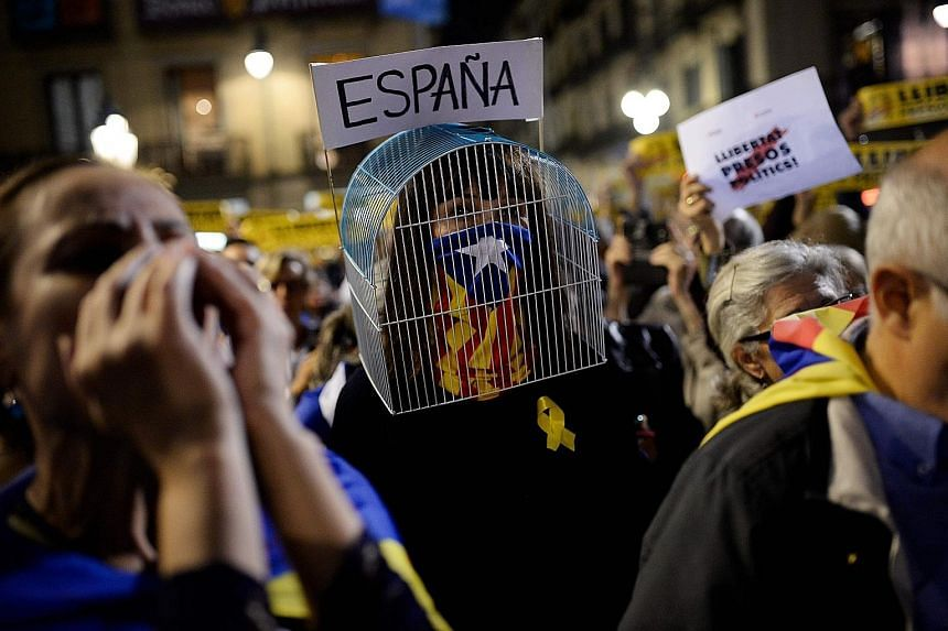 """A """"caged"""" woman, her face partly covered with a Catalan flag, taking part in a protest against the detention of former members of the regional government in Barcelona last Friday."""