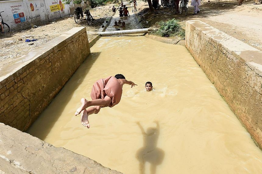 Taking a dive on a hot August day in Sibi, Pakistan, where temperatures hit a sweltering 52.4 deg C this summer. Over the past 115 years, global average temperatures have risen by about 1 deg C, according to the climate report approved for release by