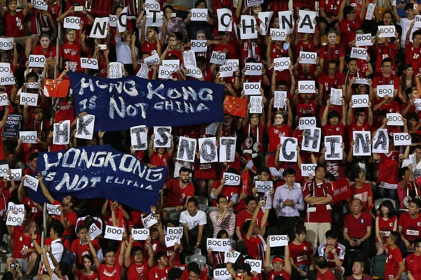 Hong Kong fans hold banners and character signs during the 2018 World Cup qualifying match between Hong Kong and China.