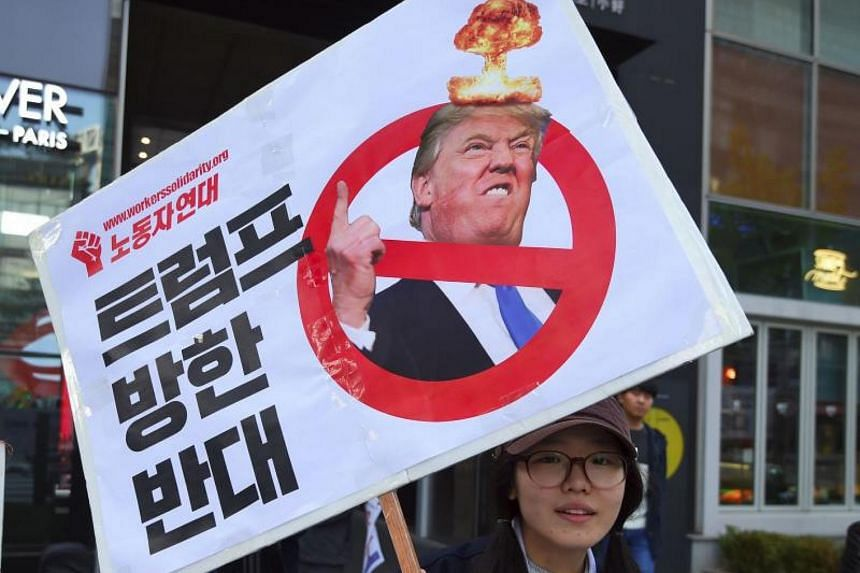 A South Korean protestor holds a placard showing a picture of US President Donald Trump during an anti-Trump rally in Seoul on Nov 4, 2017.