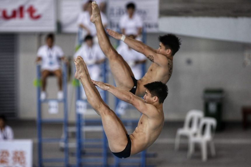 Singapore's Timothy (front) and Mark Lee performing their dive in the synchronised 3m springboard men's final in the Fina Diving Grand Prix at OCBC Aquatic Centre on Nov 5, 2017.