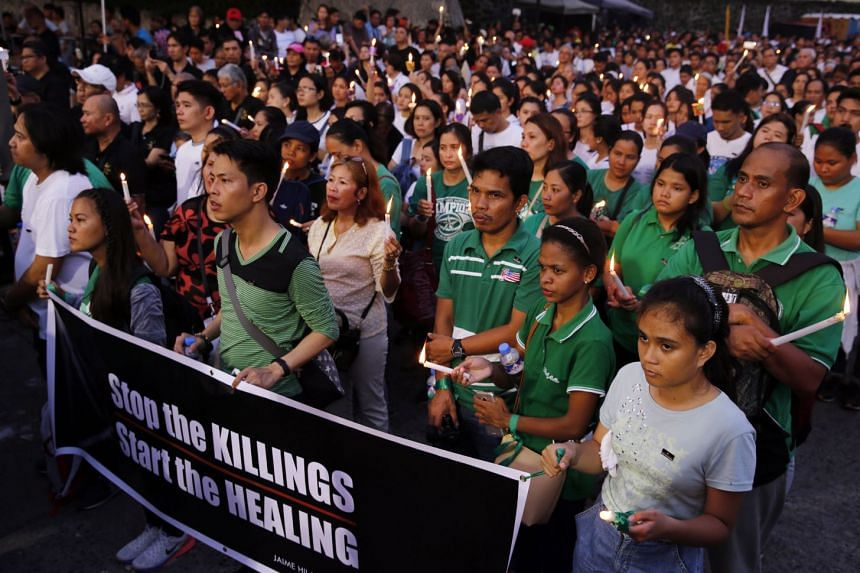 Filipinos carrying candles gathering for a demonstration calling for the end of killings as part of the drug war, in Manila on Nov 5, 2017.