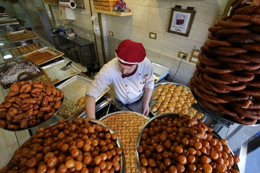 A man works at a traditional sweet shop in the northern Jordanian town of Irbid, that is owned by Syrian refugee, Mazen Obeido.