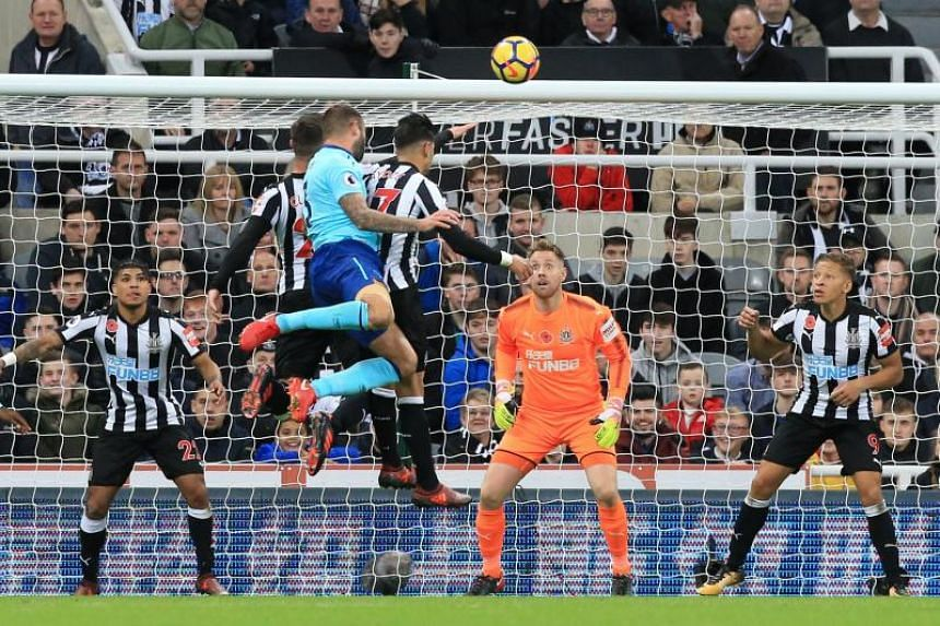 Bournemouth's English defender Steve Cook (centre) heads the ball to score past Newcastle United's English-born Irish goalkeeper Rob Elliot on Nov 4, 2017.