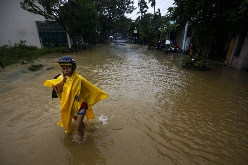 A woman wades through a flooded street in the town of Hoi An in Vietnam, on Nov 6, 2017.