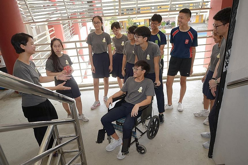 """Ms Loh Yuh Yiing (far left), 27, a policymaker, using a wheelchair to demonstrate to her """"apprentices"""" - a group of students from Xinmin Secondary School - the importance of designing inclusive policies. This was part of a workshop organised by The A"""