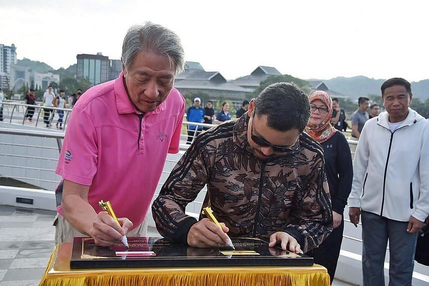 DPM Teo Chee Hean and Brunei Crown Prince Haji Al-Muhtadee Billah signing a plaque to commemorate the 5th Young Leaders' Programme at Golden Jubilee Park yesterday.