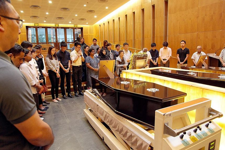 """NUS staff at the cremation of """"silent mentors"""". Donated cadavers are used for teaching for up to three years. The bodies are then cremated and the remains returned to the families. First-year medical students from the National University of Singapore"""