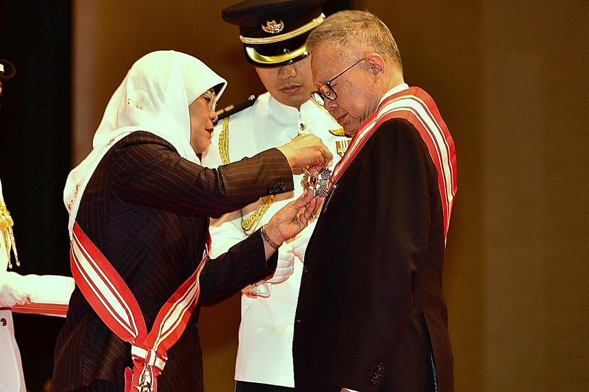 Public Service Commission chairman Eddie Teo receiving the Order of Nila Utama (First Class) from President Halimah Yacob at an awards ceremony at ITE College Central yesterday.