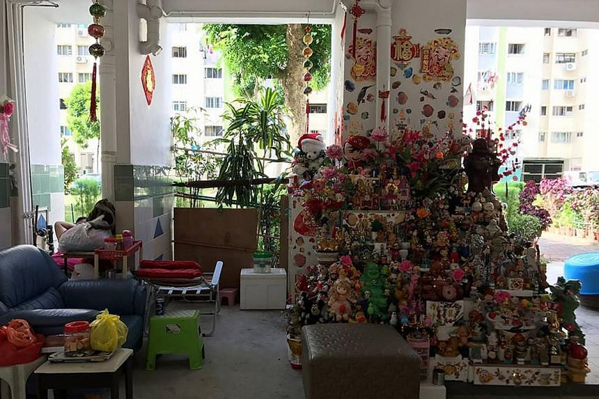 Mr Or Beng Kooi will rebuild his toy tower at The Substation with salvaged items from his original installation, as well as contributions from the public. With him are his grandson Javia Or and neighbour Wee Lai Huat. The toy tower at Block 108, Yish