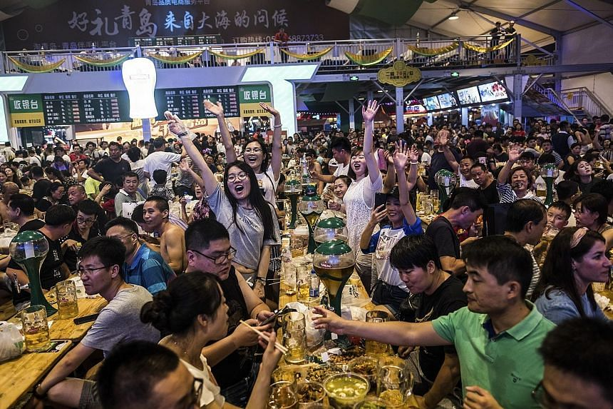 Revellers eat and drink at long tables (right) at the Qingdao International Beer Festival in Qingdao, China, an annual celebration of lager that looks similar to Germany's Oktoberfest. Celebratory events at the festival include a costume parade (abov
