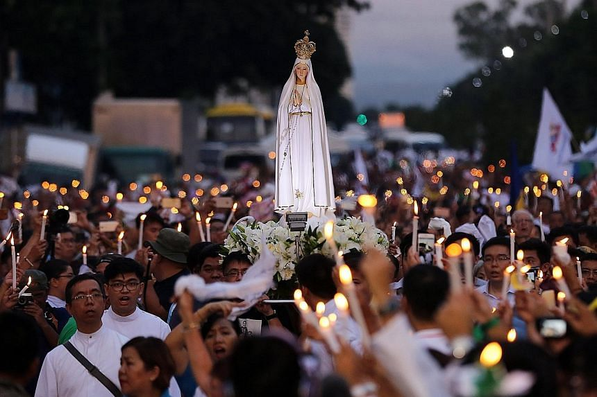 People paying tribute to victims of the anti-drug campaign at the People Power Monument in Quezon city, east of Manila, yesterday. About 3,000 people attended a mass and procession along a historic Manila highway organised by the Catholic Church.