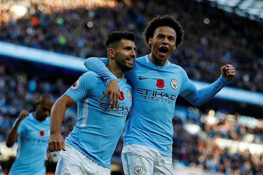 Top: Manchester City's Sergio Aguero (left) celebrates with Leroy Sane after scoring his side's second goal in the 3-1 win against Arsenal yesterday. Above: Gabriel Jesus scores the third goal for City from a cross from David Silva, who was offside d