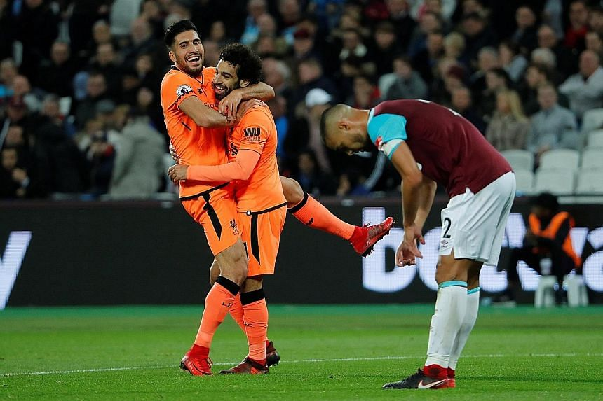 Above: A dejected West Ham manager Slaven Bilic after the hosts were defeated 4-1 by Liverpool. Left: After scoring his side's fourth goal, Liverpool's Mohamed Salah (centre) embraces team-mate Emre Can while the despair is evident in the body langua