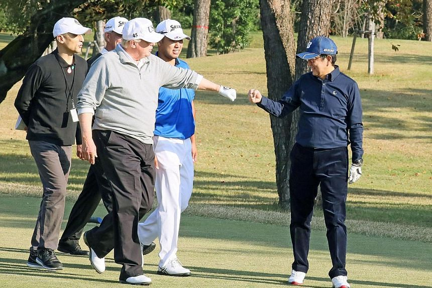 """Visiting US President Donald Trump giving Japanese Prime Minister Shinzo Abe a """"fist bump"""" as they played golf, accompanied by World No. 4 golfer Hideki Matsuyama (middle, in blue) at the Kasumigaseki Country Club in Kawagoe yesterday. Mr Abe said he"""