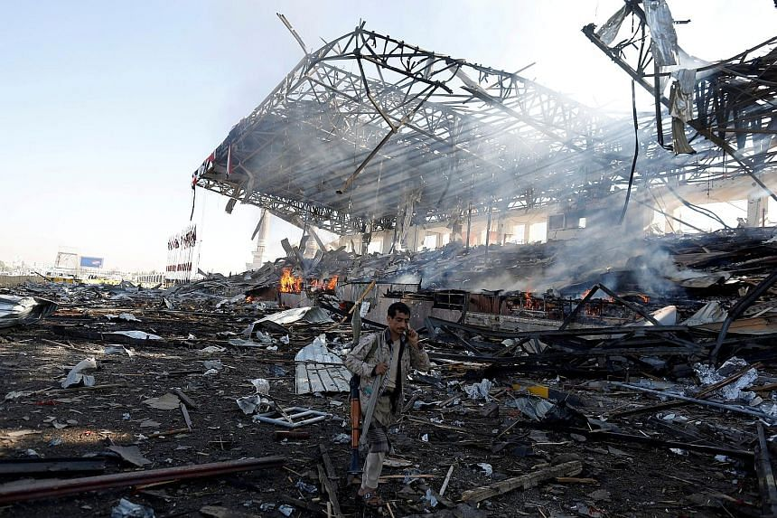A Houthi fighter at the site of an air strike on a parade square in Sanaa. About 12 strikes were heard hitting the Defence Ministry and other areas on the city outskirts.