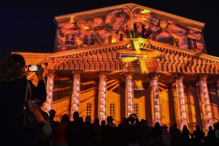 People watch a light show projected on the facade of the Bolshoi Theatre in Moscow on Sept 23, 2017, during the Circle of Light Moscow International Festival.