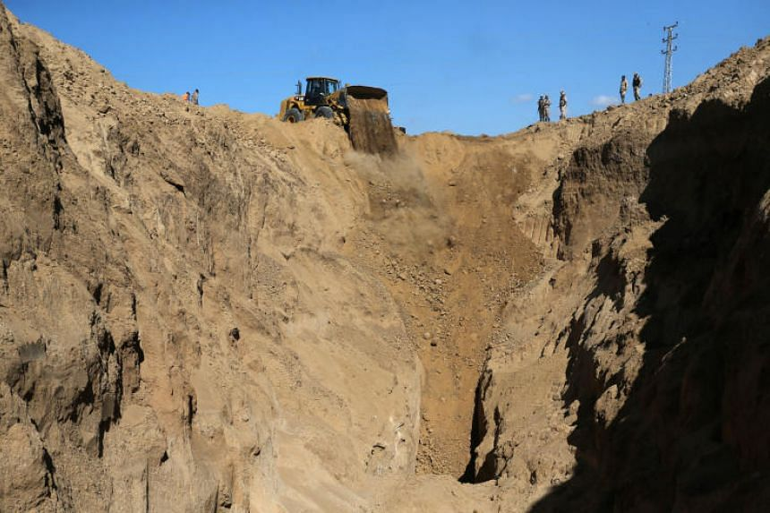 A bulldozer operates while searching for missing or dead militants after Israel blew up a cross-border tunnel, in Khan Younis in the southern Gaza Strip on Nov 3, 2017.